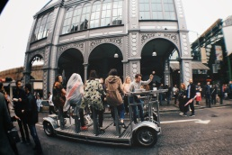 Cyclers powering a vehicle riding through the perimeter of Borough Market in London